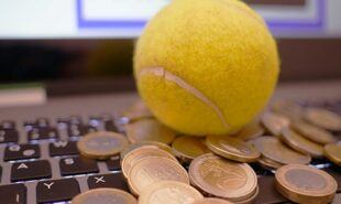 Coins and tennis ball over a laptop keyboard