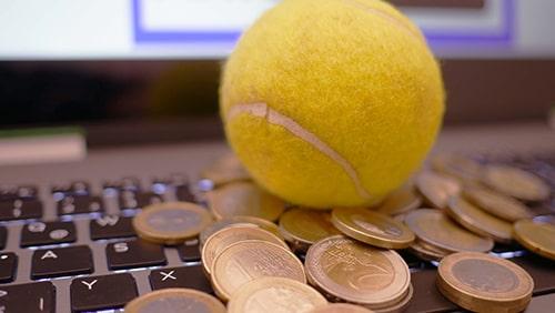 Koin dan bola tenis di atas keyboard laptop