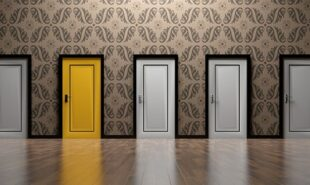 A row of closed white doors and one colored yellow