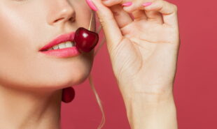 A woman with make up eating cherry