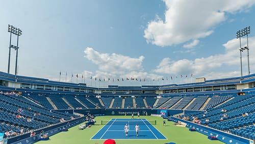 Orang-orang berdiri di lapangan tenis biru dan hijau