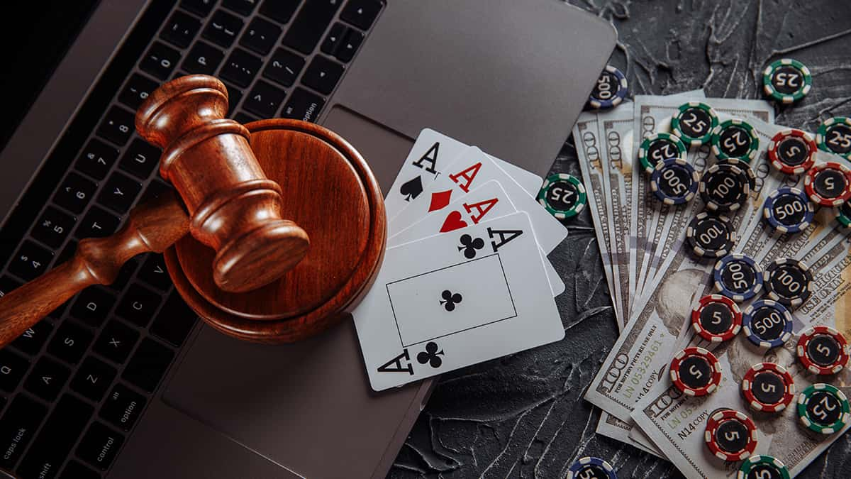 Save Download Preview Online gambling and justice theme, cards, playing chips and judge wooden gavel on laptop keyboard