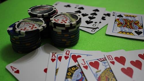 Chip kasino dan kartu di atas meja hijau
