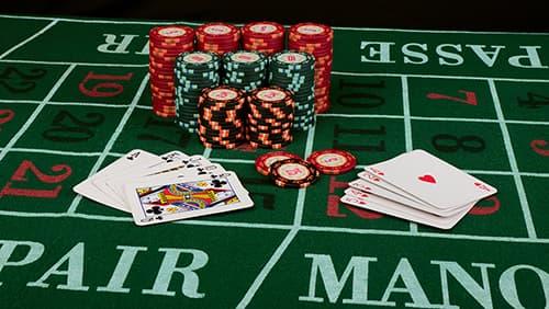 Permainan kartu kasino yang menampilkan chip dengan latar belakang kain hijau