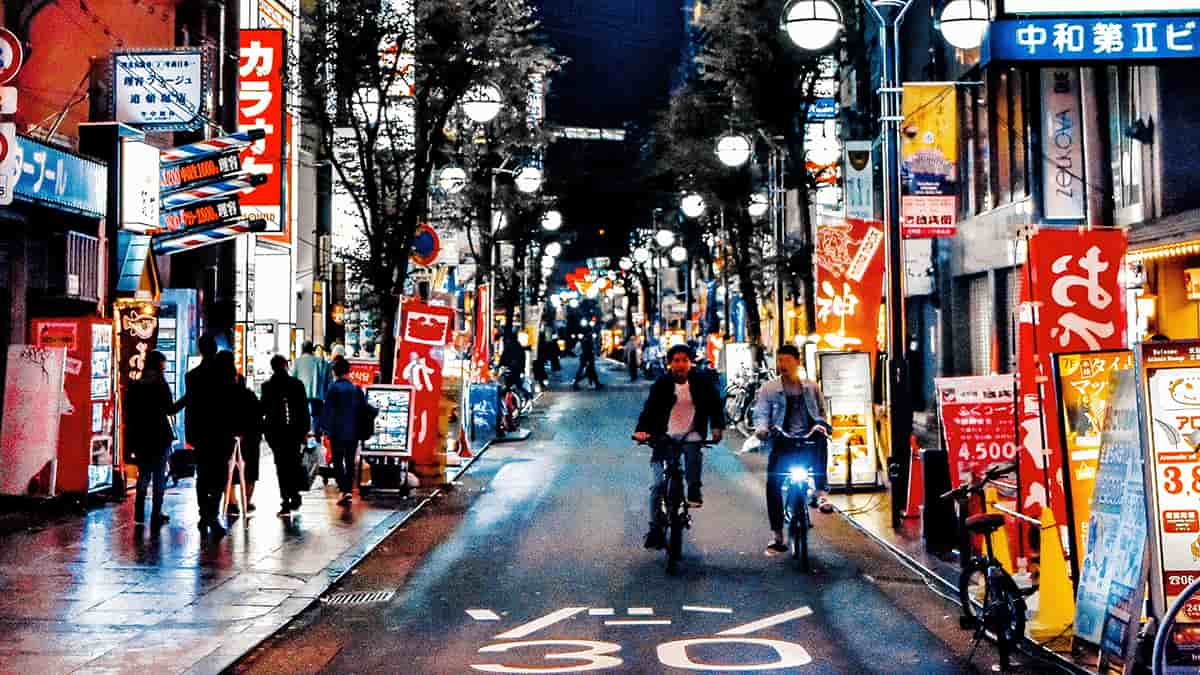 People riding the bike and walking on the side walk, night life, Japan city at night