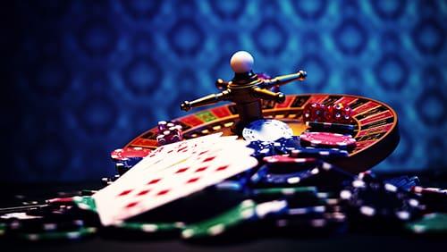 Set kasino dengan Roulette, kartu, dadu, dan chip di atas tikar BlackJack