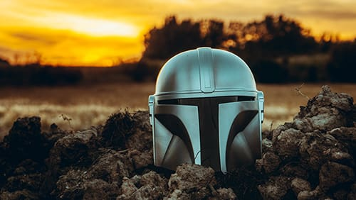 Mandalorian helmet on the ground with a sunset background