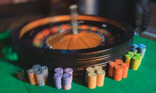 A close-up vibrant image of multicolored casino table with roulette in motion with the hand of croupier and a group of gambling rich wealthy people in the background