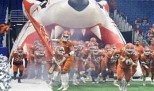 Football team running thru the football field