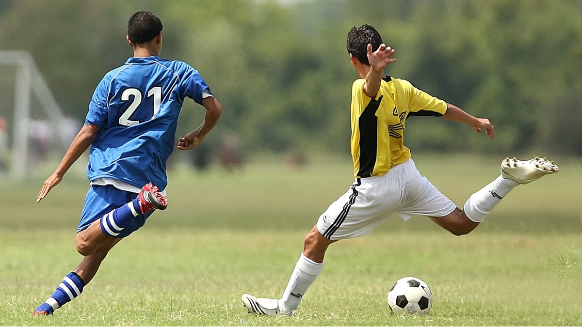 Two player in the soccer field kicking the ball