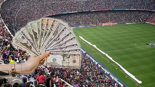 sports betting concept, holding US banknotes on a sport stadium background